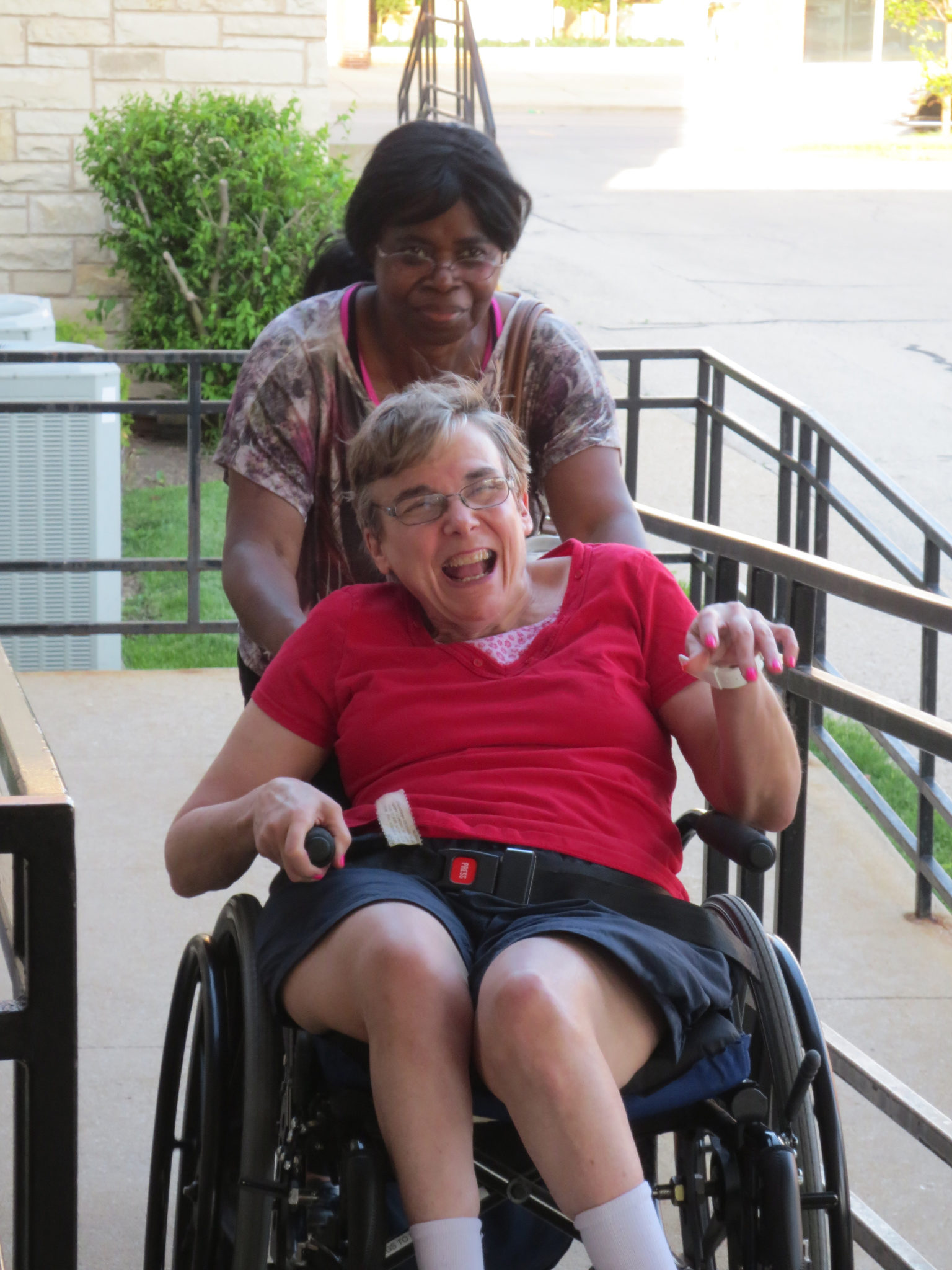 Caregiver pushing a wheelchair containing a disabled person